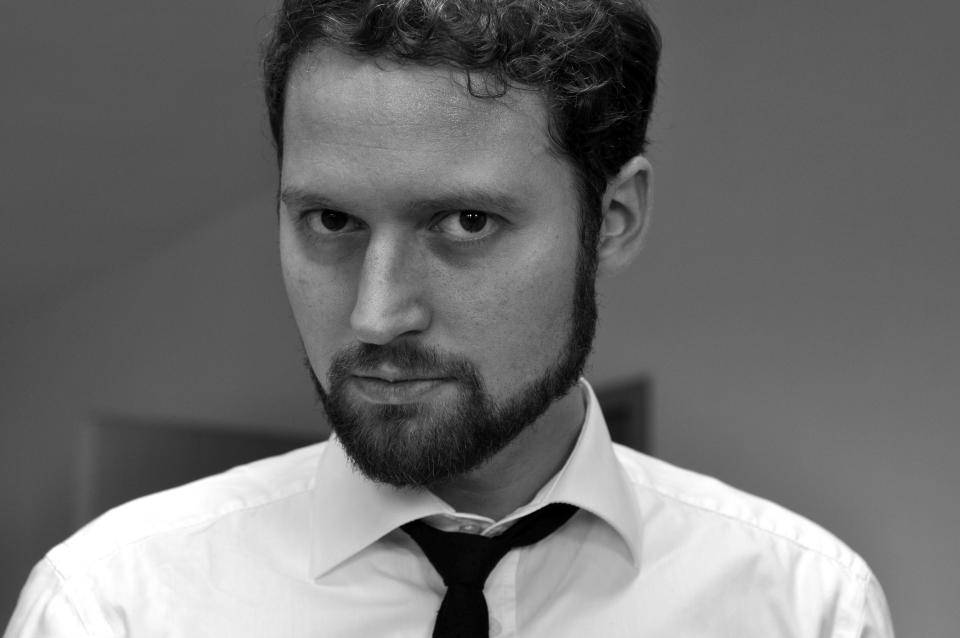 A picture of Mark Chambers, a white guy with a full beard wearing a white button-up shirt and a loosened collar and necktie.